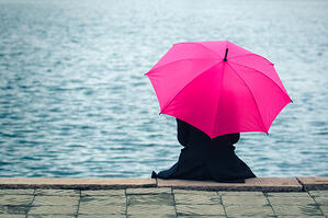 Girl with Pink Umbrella Sitting By Water