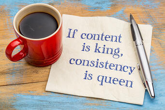 cup of coffee with napkin that has if content is king consistency is queen on it