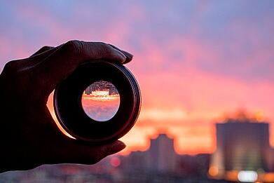Image of a person holding a lens to a city