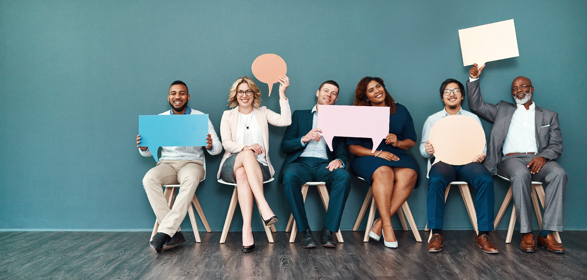 People in chairs holding up paper depictions of blank thought bubbles