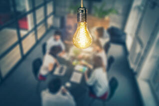 Image of a lightbulb above a meeting room