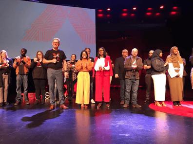 TEDX speakers on stage receiving applause